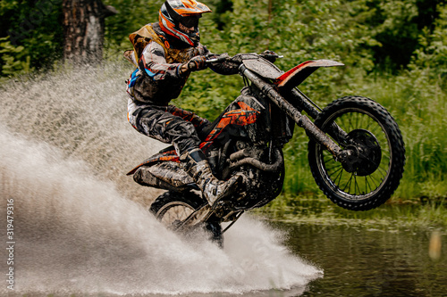 rider on motorcycle riding on back wheel in puddle of water Fototapet