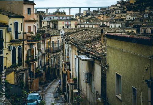 Wąska uliczka ze starymi domami i nowoczesnym wiaduktem górującym nad miastem