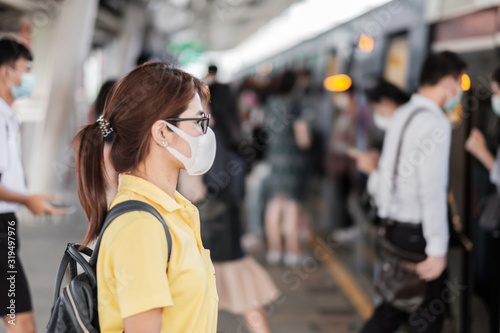 young Asian woman wearing protection mask against Novel coronavirus (2019-nCoV) or Wuhan coronavirus at public train station,is a contagious virus that causes respiratory infection.Healthcare concept - 319497976