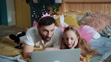 High Angle Side View Cheerful Dad And His Daughter Playing Fairies Watching Cartoons Having Fun At Home Magic Disney Party. Funny Young Family Holiday Celebration.