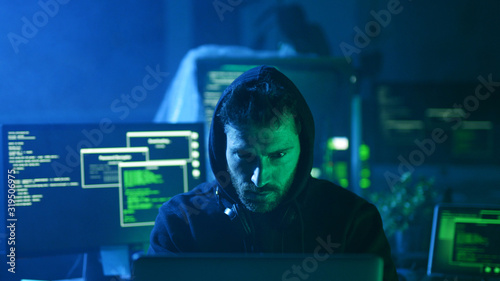 Valokuvatapetti Portrait of insidious hacker organizing virus attack on corporate servers in hideout place