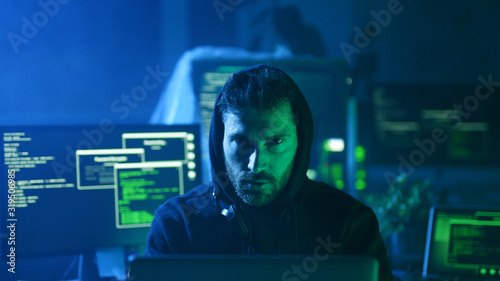 Photo Portrait of insidious hacker organizing virus attack on corporate servers in hideout place
