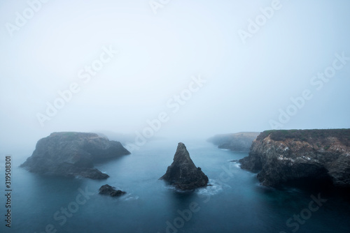 A beautiful view looking out over a foggy Mendocino Headlands State Park and the Pacific Ocean in Mendocino, California - 319508301