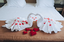 The Hotel Room Is Decorated With Swans Made Of White Towels With Red Roses Cakes And Handmade Thread Hearts. Photography, Concept, Composition.