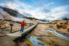 A Man Walks On The Boardwalk In Bumpass Hell, The Largest Hydrothermal Area In Lassen Volcanic National Park, California.