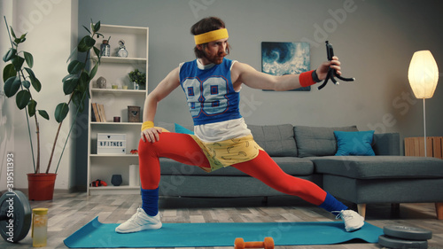 Obraz Funny-looking retro fitness instructor shooting exercise videos for vlog at home. Concentrated young man stretching legs and warming up before training. - fototapety do salonu