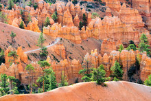 A Group Of People Hike Through Stunning Rock Formations Along The Queens Garden Trail In Beautiful Morning Light In Bryce Canyon National Park, Utah.