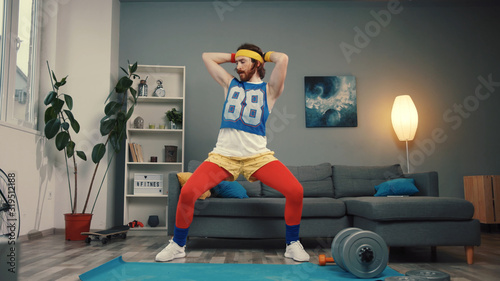 Tela Sexy aggressive young man in retro sportswear dancing with seducing moves on exercise mat on training at home