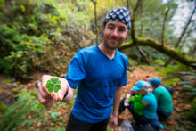A Man Stands On A Trail Smiling Holding A Four-leaf Clover While Backpacking The Lost Coast Trail In Sinkyone Wilderness State Park In Northern California.