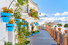 Idyllic Scenery Empty Picturesque Street Of Small White-washed Village Of Mijas. Path Way Decorated With Hanging Plants In Bright Blue Flowerpots, Costa Del Sol, Andalusia, Province Of Málaga, Spain.