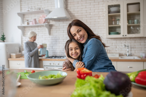 Mom and daughter hugging each other sitting at kitchen.