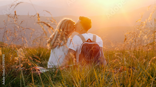 Valokuva Loving couple sitting on a mountain meadow and enjoys the view of the sunset