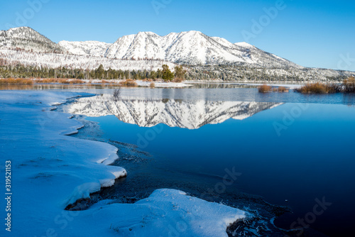 Maggies Peaks reflect in the calm water of Lake Tahoe and Taylor Creek in the winter near South Lake Tahoe, California.