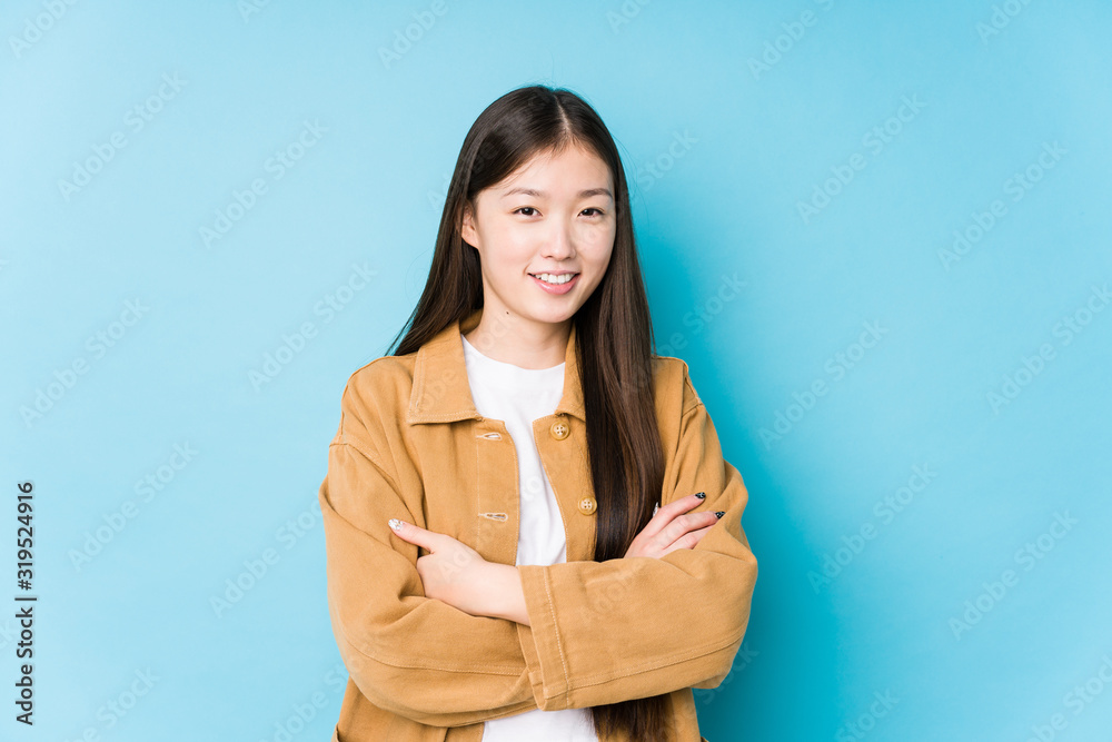 Fototapeta Young chinese woman posing in a blue background isolated who feels confident, crossing arms with determination.