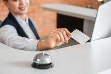 Young Female Receptionist With Card At Desk In Hotel