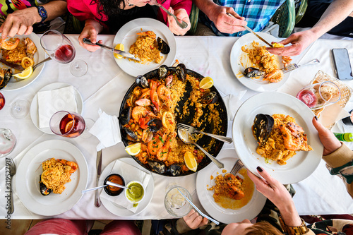Fotografiet The table in the restaurant with Spanish paella with seafood served in a pan