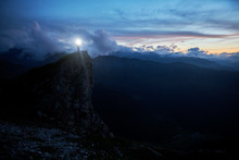 Hiker Standing On Rock Spur At Twilight, Looking At The Mountains