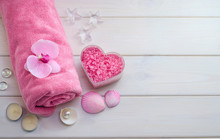 Spa Treatments As A Gift For Valentine's Day. Pink Towel With Flower, Shells And Pink Sea Salt In The Shape Of A Heart On A White Wooden Background With Copy Space. Beauty Salon