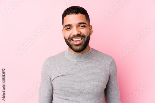 Young latin man against a pink background isolated happy, smiling and cheerful Canvas Print