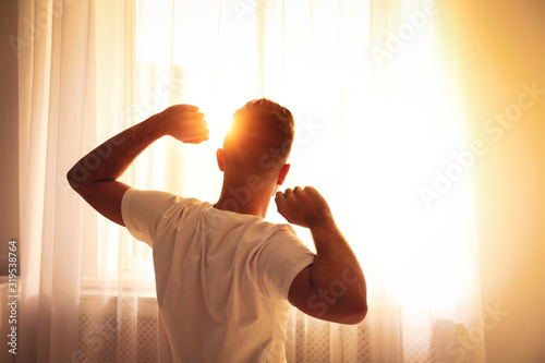 Obraz Man stretching near window at home, view from back. Lazy morning - fototapety do salonu