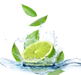 Ripe lime, fresh mint and splashing water on white background