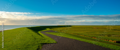 Foto typical Dutch meandere dike with cycle path and view of the Wadden Sea