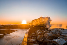 Big Waves Crashing Against The Coast And Rocks At The Tip Of The Pier During Sunset. Mighty Power Of Nature. Huge Ocean Waves.