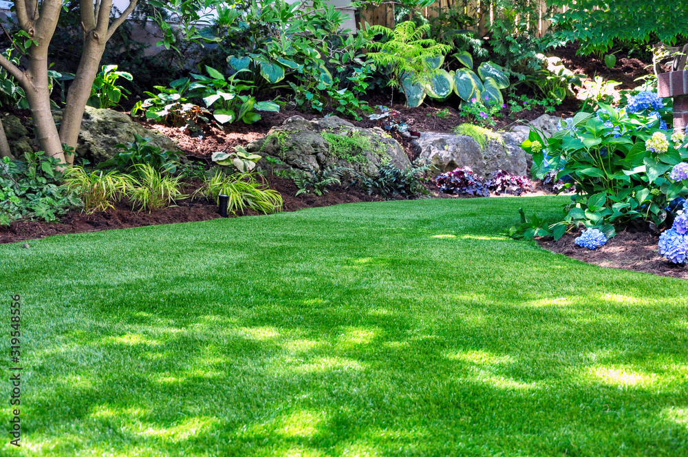 Fototapeta This beautiful backyard woodland garden features a maintenance free lawn made of natural looking artificial grass, a huge landscaping trend for small spaces.