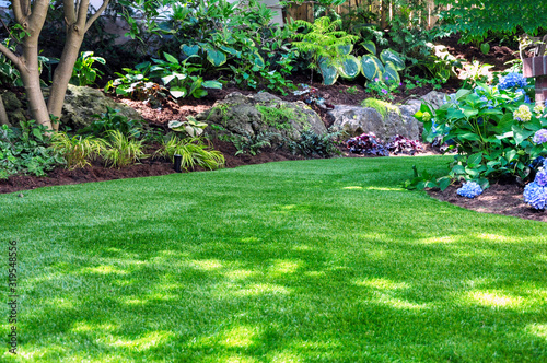 Fotomural This beautiful backyard woodland garden features a maintenance free lawn made of natural looking artificial grass, a huge landscaping trend for small spaces