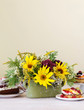 Colorful cupcakes and floral arrangement with sunflowers and hortensias