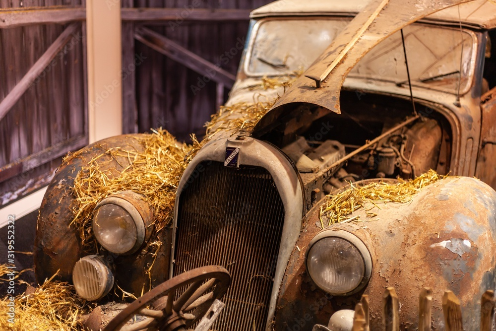 Fototapeta classic rusted car covered in hay in barn