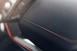 Part of stitched leather black leather car interior. Modern luxury car black perforated leather interior. Car leather interior details. Decorative seam