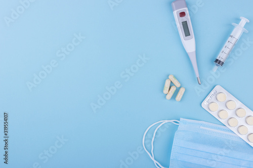 Obraz Concept image of four yellow capsule, electronic thermometer, medical mask, syringe on a blue background. Flat lay, copy space. Medicine concept seasonal illness flu, virus, runny nose, temperature. - fototapety do salonu