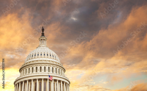 US Capitol dome with American flag and dramatic sky behind #319557914
