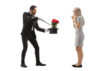 Magician Making A Magic Trick With Flowers And A Hat In Front Of A Surprised Young Woman