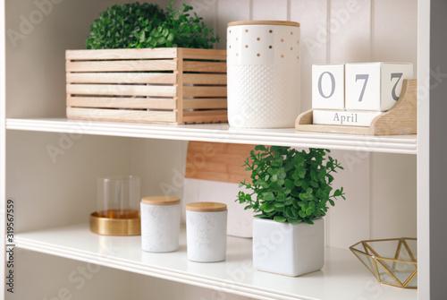 Fototapeta White shelving unit with plants and different decorative stuff obraz