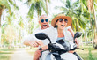 Smiling in love couple travelers riding motorbike under palm trees in their island vacation