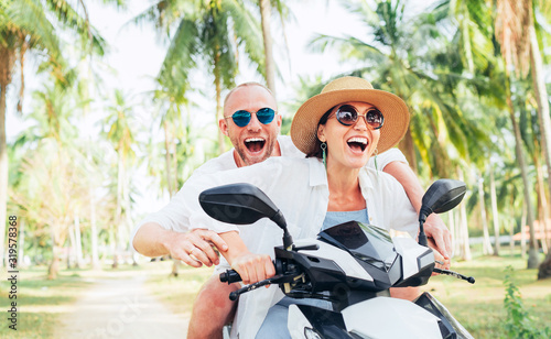 Fototapeta Smiling in love couple travelers riding motorbike under palm trees in their island vacation obraz