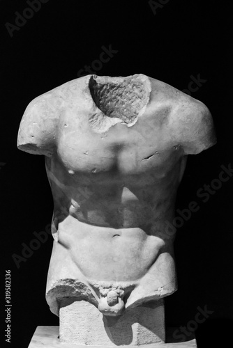 Obraz Classical roman sculpture in ruins without head and arms showing athletic male torso - black and white photo - fototapety do salonu