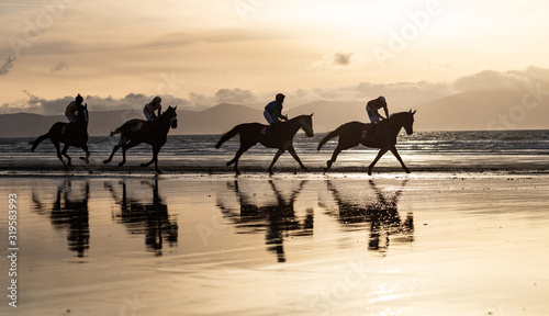 Fotomural Silhouettes of race horses and jockeys racing on the beach, wild Atlantic way on
