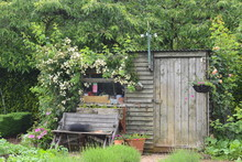 Wooden Bench Flower Hanging Basket Weather Vane Garden Potting And Storage Shed In The English Countryside Timber Used In Construction Of British Garden Furniture Originates From Sustainable Forests