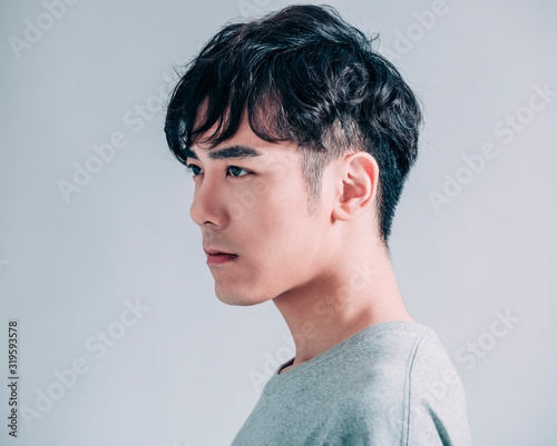 Fotomural side view of young smiling handsome man isolated on gray background