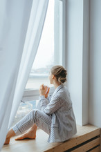 Calm Girl In Pajamas With Cup Of Tea Or Coffee Sitting And Drinking On The Window-sill At Home. Side View.