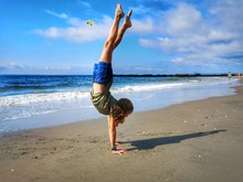 Girl Doing Handstand At Beach Against Sky