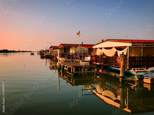 Boat House Moored At Harbor Against Sky During Sunset Fotobehang