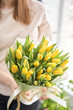 Young beautiful woman holding a spring bouquet of yellow tulips in her hand. Bunch of fresh cut spring flowers in female hands