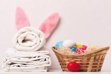 A Close-up Of A Stack Of Clean White Bedding, Towels And Easter Bunny Ears, A Basket Of Eggs On A Table, Against A Background Of Light Walls