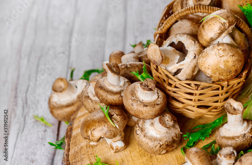 Brown portobello champignon in wicker basket on a wooden table.