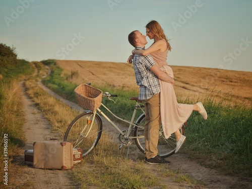 Side View Of Romantic Boyfriend Carrying Girlfriend While Standing On Field Against Sky