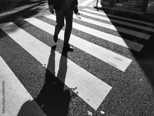 Low Section Of Man Walking On Zebra Crossing Fototapet